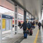 Zdjęcie przedstawia pasażerów korzystających zestacji Lublin Główny. Wtle widać stojący pociąg.