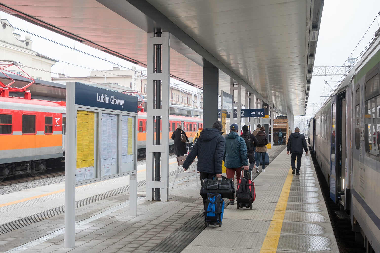 Zdjęcie przedstawia pasażerów korzystających ze stacji Lublin Główny. W tle widać stojący pociąg.