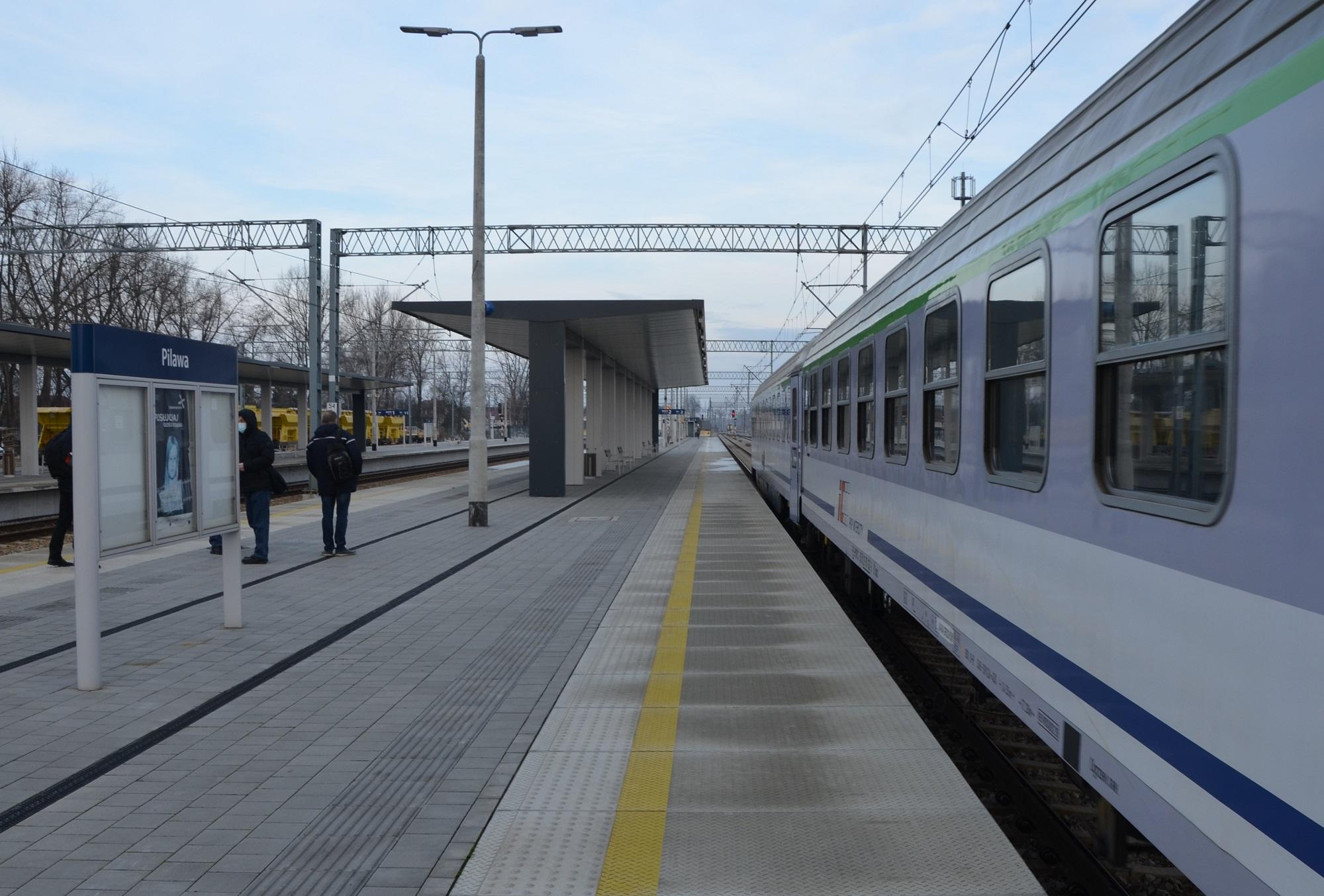 Na zdjęciu widać zmodernizowaną infrastrukturę pasażerską. Peron wyspowy w Pilawie wyposażony jest w duże wiaty, nowe tablice informacyjne, oświetlenie i ławki z których korzystają pasażerowie. Po drugiej krawędzi peronu widać pociąg.