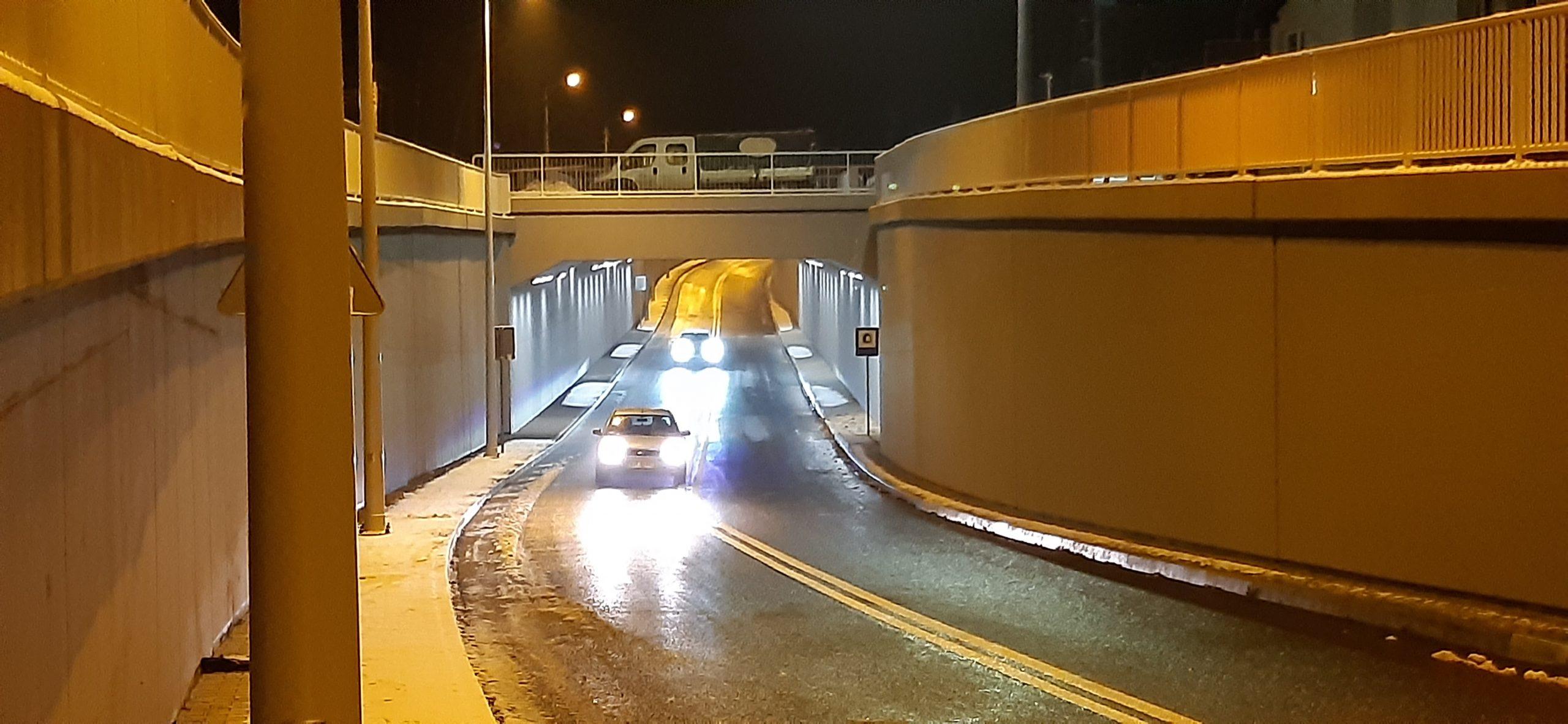 Zdjęcie przedstawia wiadukt drogowo - kolejowy wOtwocku przy ul.Żeromskiego orazjadący podnim samochód osobowy. Zmodernizowany obiekt wygląda nowocześnie. Podwiaduktem zamontowane jest oświetlenie.